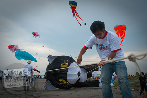 sejumlah peserta menyiapkan layang-layang yang akan diterbangkan di pantai parangkusumo, bantul, yogyakarta
