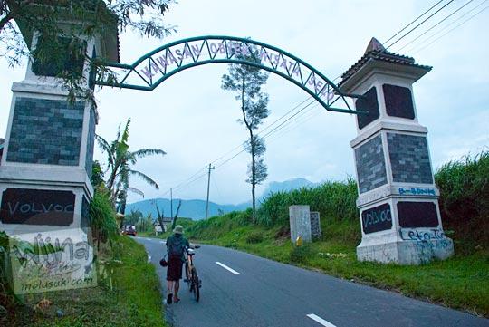 bersepeda melewati gapura selamat datang di kawasan obyek wisata Selo di Boyolali, Jawa Tengah