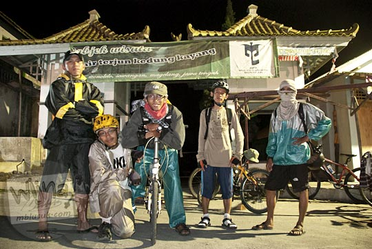 pesepeda berpose di depan gerbang masuk ke obyek wisata Air Terjun Kedung Kayang di Ketep, Magelang saat bersepeda malam hari dari Selo