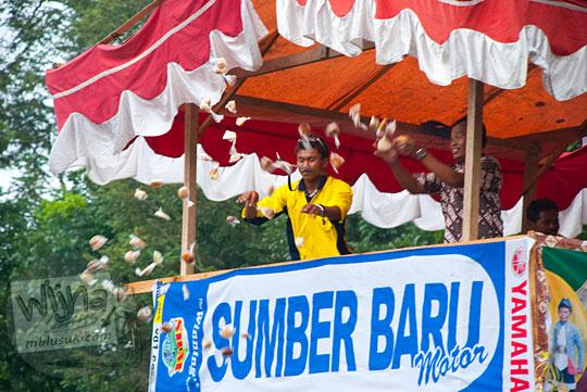 aksi lempar kue apem dari panitia upacara saparan pondok wonolelo kepada pengunjung