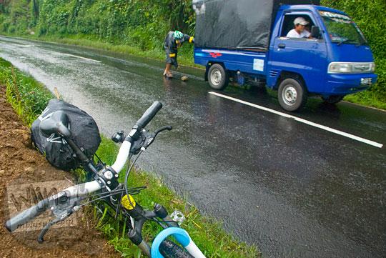 Pesepeda membantu mobil pickup yang kesulitan menanjak saat bersepeda dari Wonosobo ke Dieng pada tahun 2010