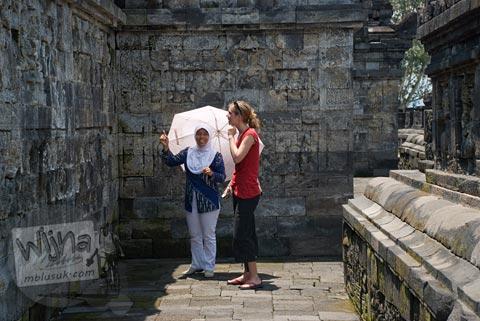 Foto turis asing dipandu pemandu lokal mempelajari sejarah Candi Borobudur, Magelang, Jawa Tengah pada tahun 2009