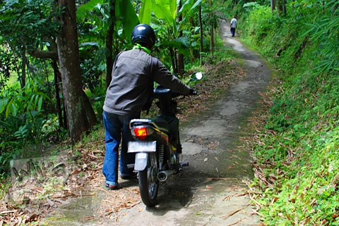 Menuntun sepeda motor menuju Candi Ngempon di Ungaran, Jawa Tengah karena jalannya licin dan terjal