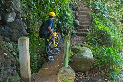 mengangkat sepeda lipat menuruni tangga menuju Curug Dago di Bandung pada tahun 2010