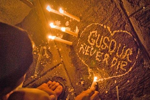 Seorang Pemuda mengukir nama Gus Dur menggunakan lilin
