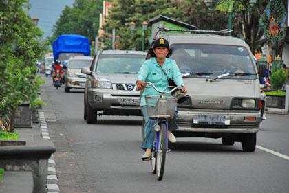 Wanita bersepeda di jalan raya Kota Jogja sendirian