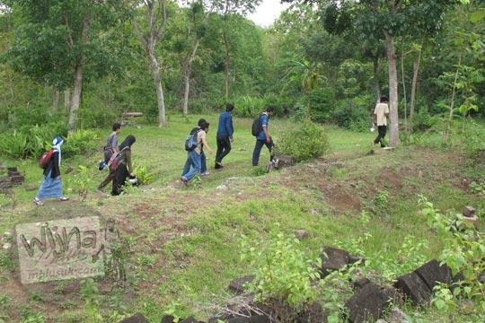 sekelompok orang berjalan kaki melewati situs dawangsari prambanan