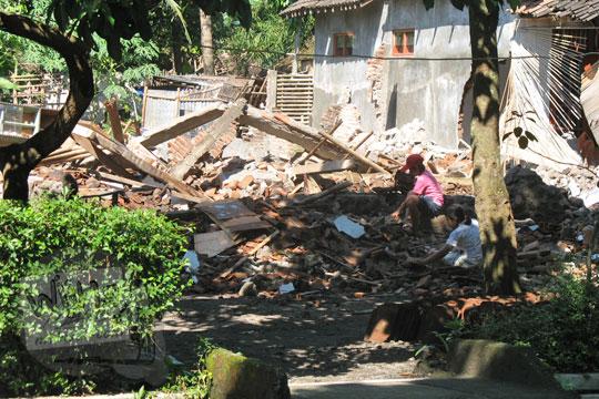 warga desa kebondalem kidul di prambanan klaten sedang menyelamatkan harta benda di rumah yang rubuh terkena gempa 2006