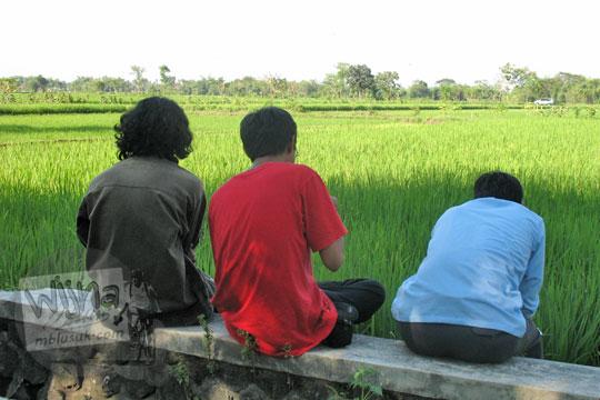 pemuda desa duduk menghadap sawah