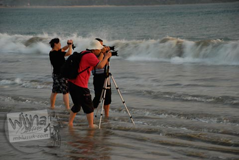 Foto aksi fotografer mengabadikan foto senja dari Pantai Jimbaran, Bali pada Agustus 2009