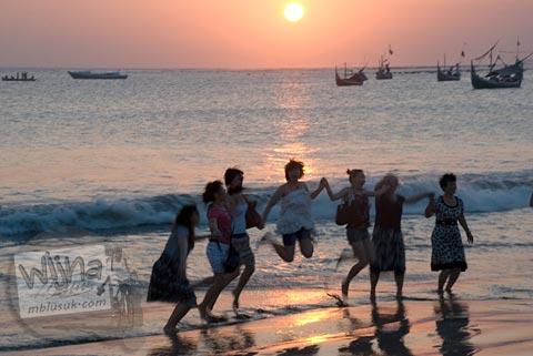 Foto wisatawan asing wanita berpose di Pantai Jimbaran, Bali saat senja pada Agustus 2009