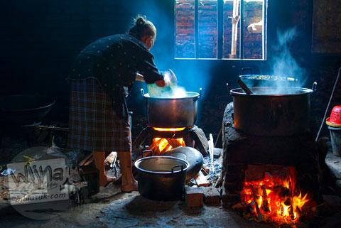 Foto Mbah Marto pemilik Sega Gudeg Nggeneng, Bantul yang terkenal dengan Mangut Lelenya sedang memasak di dapur rumahnya tahun 2010