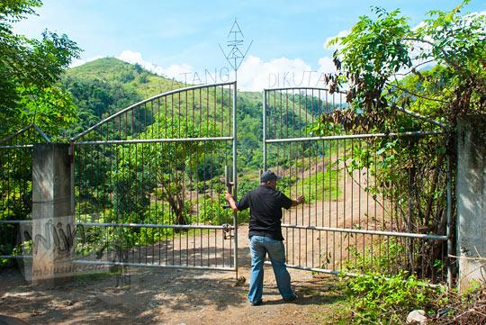 foto pria membuka gerbang masuk air terjun Kuta Malaka, Aceh Besar pada zaman dulu september 2014