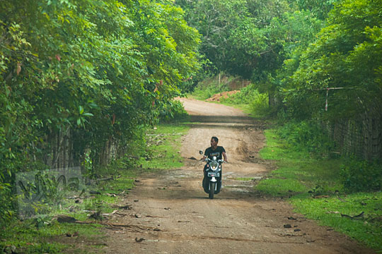 foto pria naik sepeda motor melintasi jalan hutan di kuta malaka, Aceh Besar pada zaman dulu september 2014