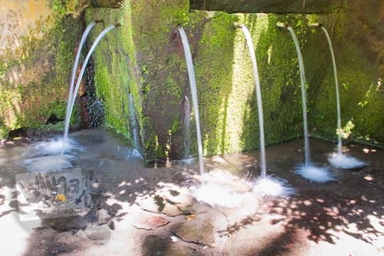 pancuran air keramat yang mengalir dari air terjun Tegenungan, Bali