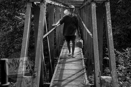 pria tua kakek merokok di jembatan kayu payaman di argorejo, sedayu, bantul zaman dulu pada tahun 2011