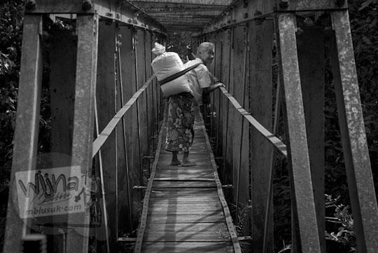 nenek tua memikul karung menyeberangi jembatan kayu payaman di argorejo, sedayu, bantul zaman dulu pada tahun 2011