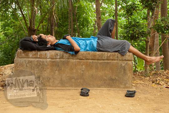 pria berkaos biru tidur kelelahan di buk ketika bersepeda menanjak gua cerme, bantul. yogyakarta