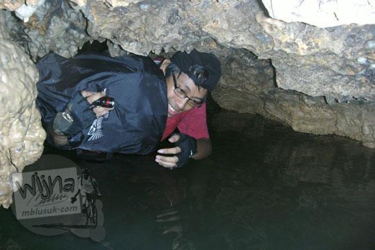 cowok kaos merah menyeberangi sungai setinggi dada di dalam gua cerme
