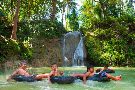 Anak-anak bermain di kolam Kedung Pengilon, Bantul menggunakan ban dari ban truk bekas yang disewakan seharga Rp5000 sepuasnya