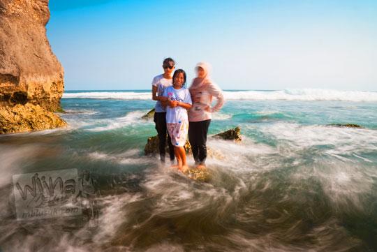 tiga orang perempuan cewek berpose dan berfoto di atas karang dikelilingi ombak laut Pantai Indrayanti atau Pantai Pulang Syawal Gunungkidul pada zaman dulu bulan Juli 2012