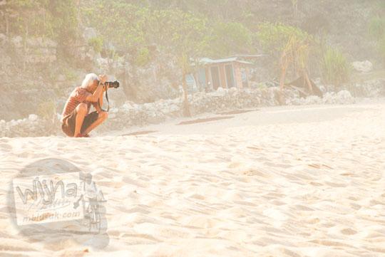 Fotografer noes prapsiyamta moeksan berburu foto di Pantai Pok Tunggal, Gunungkidul