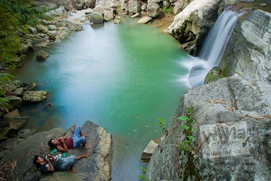 Dua pria sedang tidur sambil memancing di kolam yang ada di dekat air terjun