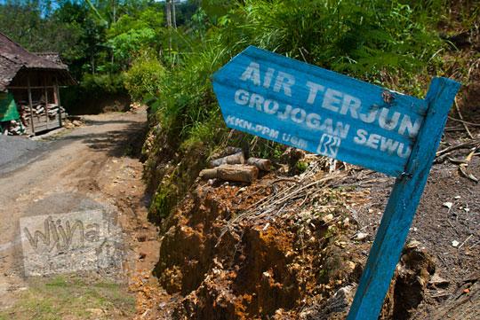 papan arah berwarna biru disponsori bri yang mencantumkan arah menuju Grojogan Sewu, Kulon Progo karya mahasiswa KKN yang disponsori bank BRI
