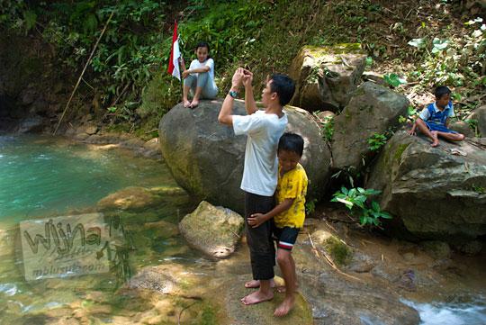 anak kecil memeluk cowok yang sedang memotret di Grojogan Sewu Beteng Girimulyo Kulon Progo