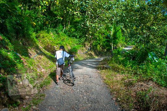 Jalan desa berwujud jalan aspal rusak yang ada di suatu dusun di Kecamatan Girimulyo, Kulon Progo pada zaman dulu April 2014