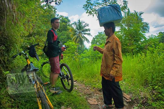 Seorang warga di pelosok Girimulyo, Kulon Progo membawa barang bawaan di atas kepalanya pada zaman dulu April 2014