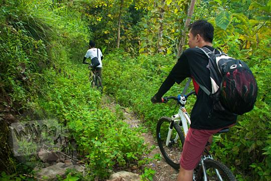 Menembus jalan semak belukar dengan sepeda mengelilingi Bukit Kayangan di Kecamatan Girimulyo, Kulon Progo, Yogyakarta pada zaman dulu April 2014