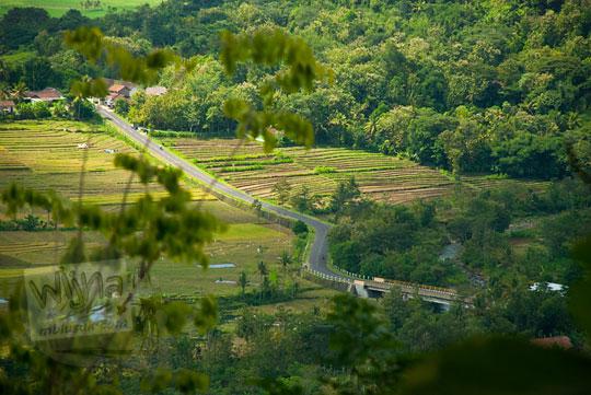 Pemandangan jalan raya di Girimulyo, Kulon Progo, Yogyakarta yang dikeliling sawah dilihat dari puncak Bukit Kayangan pada zaman dulu April 2014