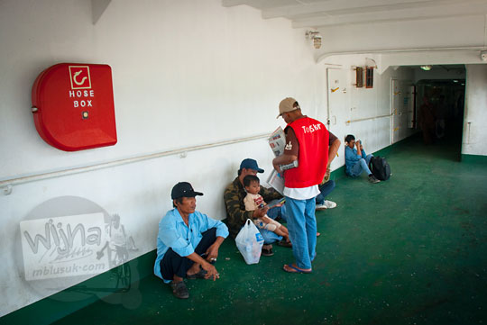 penumpang membeli koran bekas dari penjual di atas kapal Ferry Virgo 18 tujuan Pelabuhan Bakauheni, Lampung yang digunakan sebagai alas duduk pada zaman dulu Maret 2015