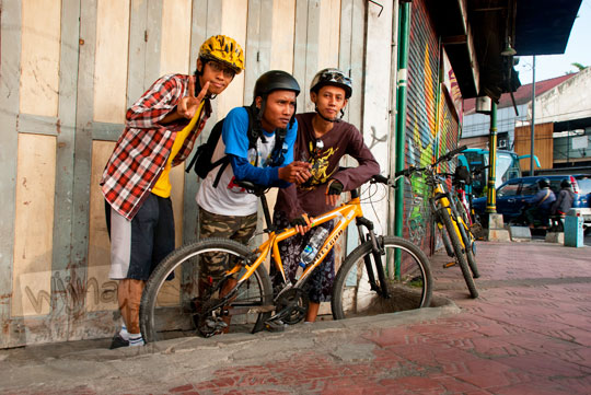 foto pesepeda pria berfoto bareng di depan toko besi di kawasan tugu pal putih kota yogyakarta pada zaman dahulu