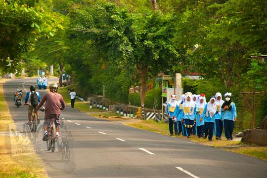 foto sekumpulan siswi berseragam smp sedang berolahraga joging di jalan raya kalibawang magelang