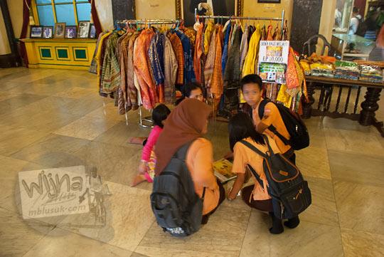 Wisatawan SMP di Istana Maimoon Medan sedang menyewa pakaian adat untuk berfoto