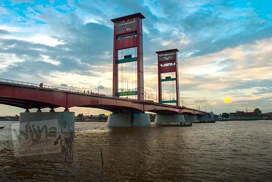 Foto indah Jembatan Ampera yang membentang di atas Sungai Musi berlatar awan mendung yang dipotret dari kawasan Plaza Kuto Besak pada tahun 2015