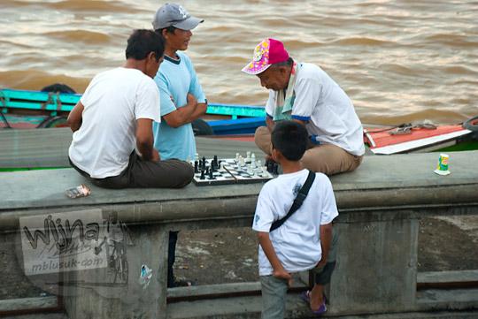 dua orang bapak warga sedang bermain catur di kawasan Plaza Kuto Basak dekat Tepian Sungai Musi Palembang pada tahun 2015