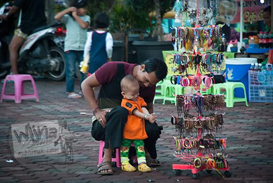 abang pedagang kaki lima penjual aksesoris sedang mengasuh anak laki-lakinya di kawasan Plaza Kuto Basak dekat Tepian Sungai Musi Palembang tahun 2015