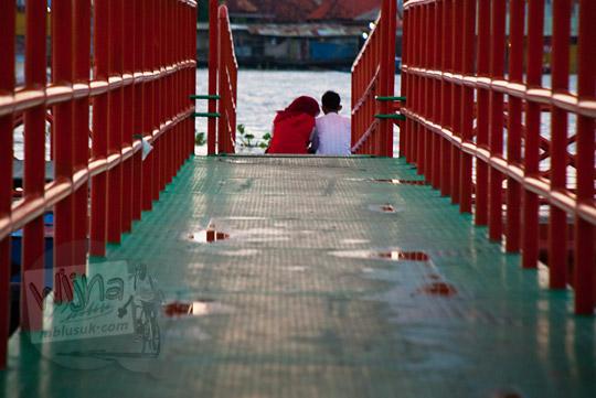 cowok baju merah dan cewek Palembang berjilbab sedang pacaran di kawasan Plaza Kuto Basak dekat Tepian Sungai Musi Palembang pada tahun 2015