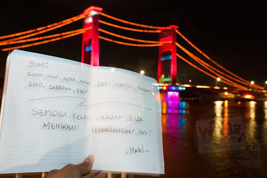 Ucapan doa ditulis di kertas berlatar jembatan Ampera pada malam hari yang dipotret dari kawasan Plaza Kuto Basak dekat Tepian Sungai Musi Palembang pada tahun 2015
