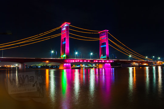Jembatan Ampera dan refleksi pantulan cahaya lampu pada malam hari dipotret dari kawasan Plaza Kuto Basak dekat Sungai Musi Palembang tahun 2015