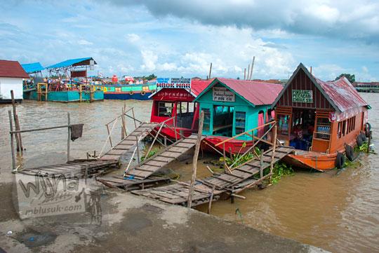 Warung apung yang menjual aneka makanan bersaing secara sehat di atas Sungai Musi di Palembang Sumatra Selatan