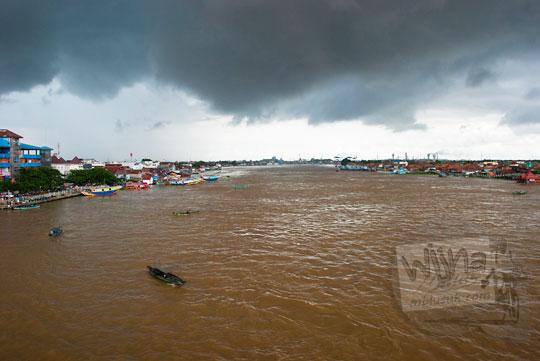 Penampakan Sungai Musi di Kota Palembang Sumatra Selatan yang tercemar dan berwarna cokelat keruh dengan latar awan mendung
