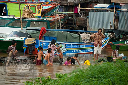 Anak-anak, orang tua, serta gadis muda yang tinggal di pemukiman di Tepi Sungai Musi mandi telanjang di Sungai Musi Palembang Sumatra Selatan