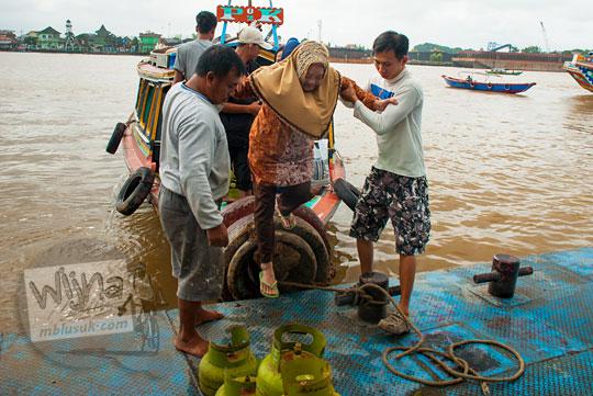 Aktivitas naik turun penumpang perahu yang berlayar di Sungai Musi di Kota Palembang, Sumatra Selatan