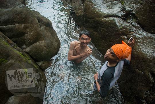 Muhammad Angki Prasetyo Nugroho telanjang dada menyebur ke sungai menuju Curug Klanceng Putih, Sedayu, Purworejo