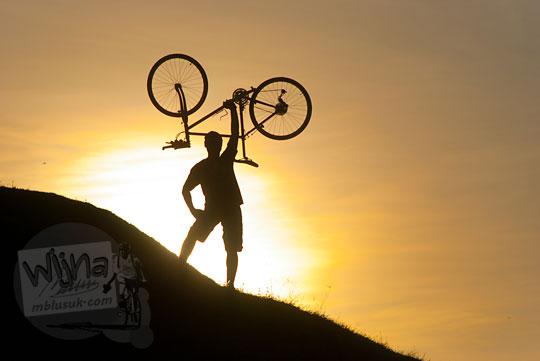 Foto siluet seorang pria menangkat sepeda mtb gunung di puncak Candi Abang Jogotirto Berbah Sleman pada zaman dahulu Mei 2012