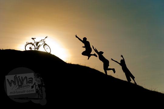 Foto siluet tiga pria melompat ke sepeda di puncak Candi Abang Jogotirto Berbah Sleman pada zaman dahulu Mei 2012